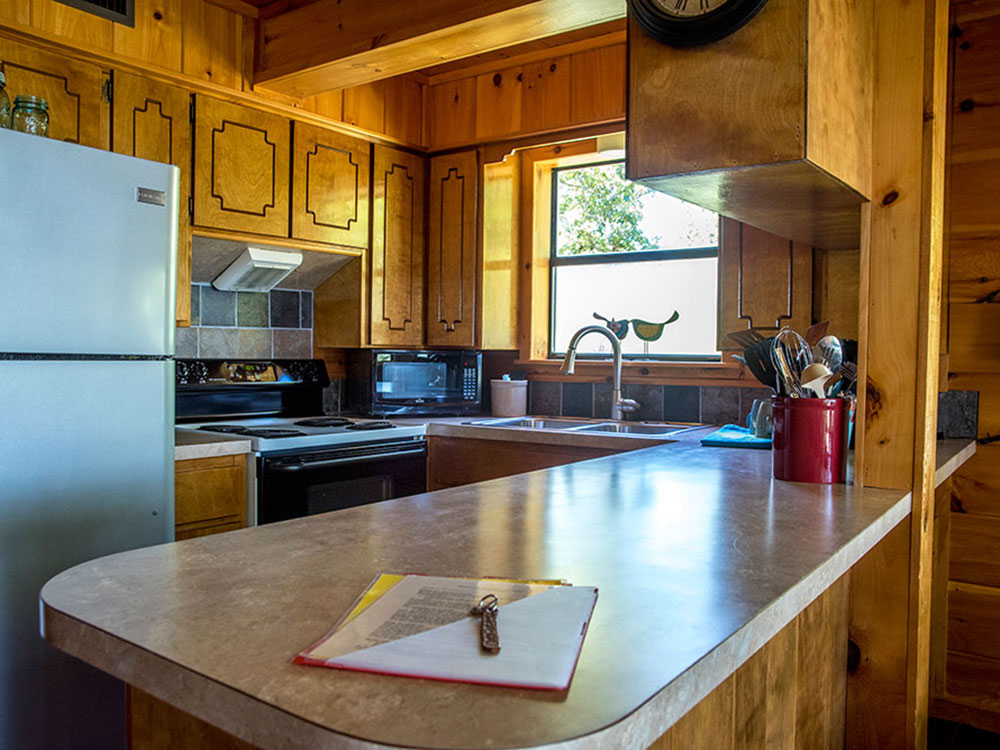 The Sunrise Cabin rental comes with a full kitchen at Peckerwood Knob Cabins in Oklahoma